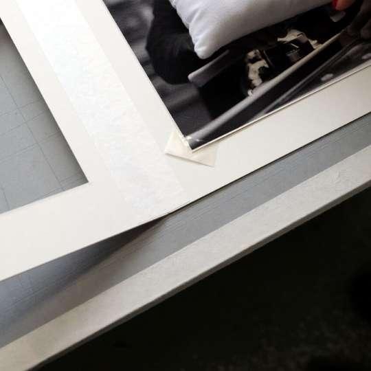 Einmaligen Exponate sowie Grafiken mit Signatur benötigen eine freigestellte Rahmung mit Klapp-Passepartout, d. h. das Motiv wird auf dem Rückwandkarton des Passepartouts beispielsweise mit transparenten Fotoecken exakt in den Passepartout-Ausschnitt positioniert.