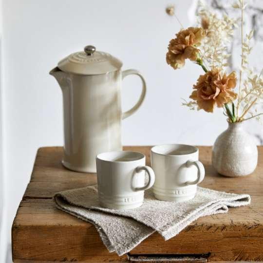 Le Creuset: Meringue Kaffeezubereiter und Becher neben Blumenvase