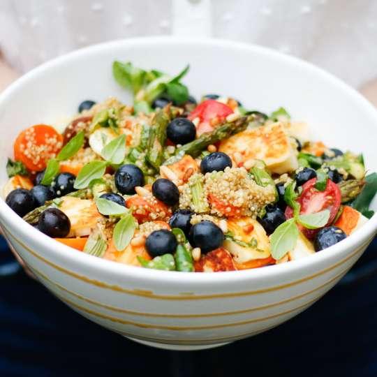 Bunter Quinoa-Salat mit geröstetem Frühlingsgemüse, Halloumi und Heidelbeeren
