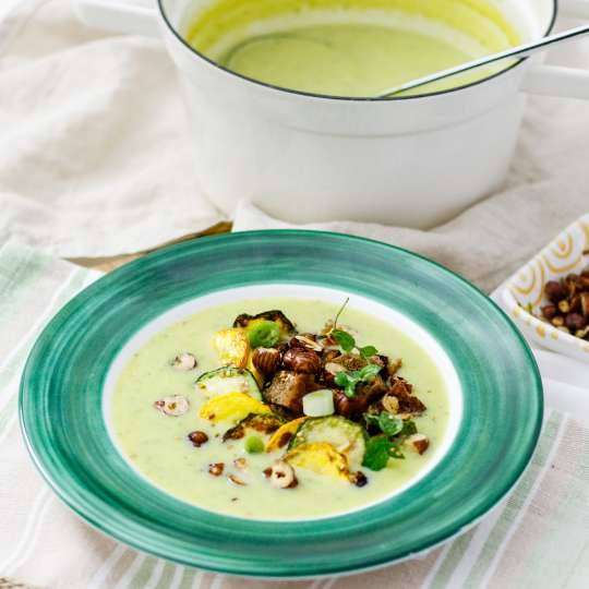 Suppenteller mit Zucchinisuppe vor Suppenterrine