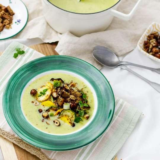 Suppenteller mit Zucchinisuppe auf Tischset